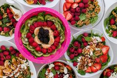 Bowls of assorted fresh salads with fruit and nuts royalty free stock photography