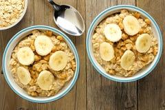 Bowls of banana walnut oatmeal on wood Stock Photos