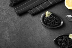 Bowls with black caviar on grey background. Bowls with black caviar on dark grey background Royalty Free Stock Photo
