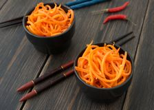 Bowls of bright orange spicy carrots Korean salad. Red peppers and chopsticks on dark rustic wooden table background close-up Royalty Free Stock Photo