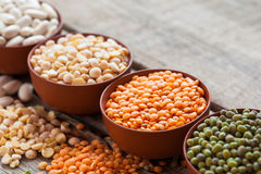 Bowls of cereal grains. Red lentils, green mung, corn, beans and peas on wooden kitchen table. Selective focus Stock Photography