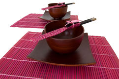 Bowls And Chopsticks. Two sets of bamboo plates, bowls and chopsticks on pink place mats isolated over white Stock Photography