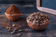 Bowls of coffee beans and ground coffee and menu board Royalty Free Stock Images