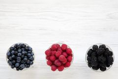 Bowls containing berries: blueberries, blackberries, raspberries, top view. Healthy eating and dieting. From above, overhead. Copy space Stock Images