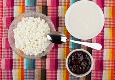 Bowls with cottage cheese, strawberry jam, sour cream and spoon Stock Photos