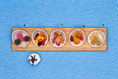 Bowls of different gummy candies. With crystalised sugar coating, jujubes, jelly beans and fruity gums arranged in a row on a wooden board centered on a blue Stock Images