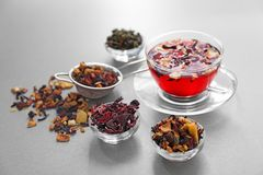 Bowls with different types of dry tea leaves and cup of aromatic beverage on light background royalty free stock photo