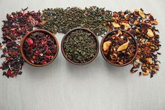 Bowls with different types of dry tea leaves on light background stock photo