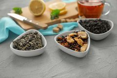 Bowls with different types of dry tea leaves on table stock image