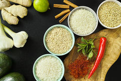 Bowls with different types of rice, vegetables and spices Stock Photo