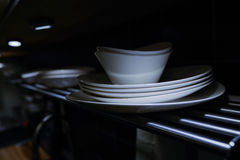 Bowls and dishes on steel rack in kitchen Royalty Free Stock Image