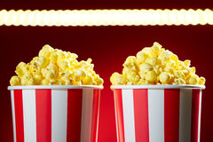 Bowls Filled With Popcorn For Movie Night Red Background. Two red bowls full of popcorns on red background for film, TV, television watching. Concept of couple Stock Photo