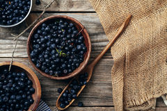 Bowls with forest blueberry just picked. Three bowls with forest blueberry just picked and kept unwashed. Wooden rustic background, linen and striped towel Stock Image