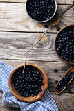 Bowls with forest blueberry. Three bowls with forest blueberry just picked and kept unwashed. Wooden rustic background, linen and striped towel. Harvest. Top Royalty Free Stock Images