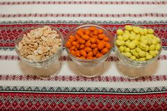Bowls of fresh colored peanuts on a red tablecloth.  Royalty Free Stock Image