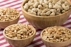 Bowls of fresh peanuts on a red checkered tablecloth Stock Photos