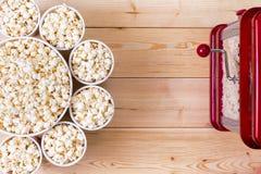 Bowls of fresh popcorn alongside a machine stock images