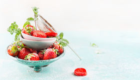 Bowls with fresh Strawberries and sugar strainer on light blue background Royalty Free Stock Photo