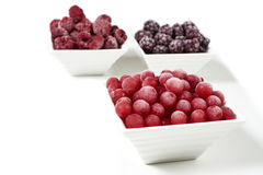 Bowls with frozen berries on white background Stock Photos