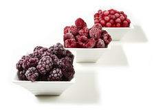 Bowls with frozen berries on white background Stock Photography