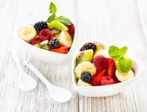 Bowls with fruits salad. On a old wooden table royalty free stock photos