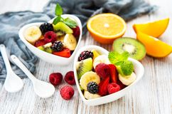 Bowls with fruits salad. On a old wooden table royalty free stock images