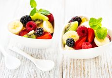Bowls with fruits salad. On a old wooden table royalty free stock photo