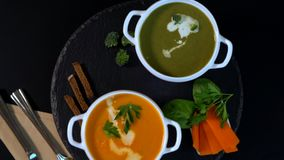 Bowls of gourmet homemade vegetable soup. With pumpkin or butternut and spinach and broccoli garnished with cream revolving on a carousel stock video