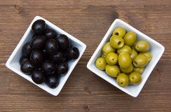 Bowls with green and black olives on wood from above Stock Images