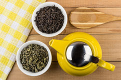 Bowls with green and black tea, teapot and bamboo spoon Stock Images