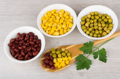 Bowls with green peas, beans, sweet corn, parsley and spoon Stock Photography