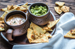 Bowls of guacamole and queso with tortilla chips Royalty Free Stock Images