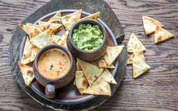 Bowls of guacamole and queso with tortilla chips Stock Photos