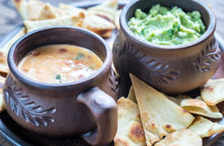 Bowls of guacamole and queso with tortilla chips Royalty Free Stock Photos