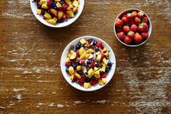 Bowls of healthy organic muesli with fruits on dark wooden table stock images