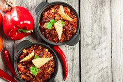 Bowls of hot chili con carne with ground beef, beans, tomatoes a Stock Photography