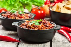 Bowls of hot chili con carne with ground beef, beans, tomatoes and corn Stock Images