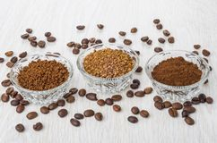 Bowls with instant and ground coffee, coffee beans on table Stock Image