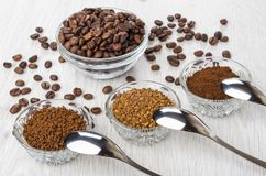 Bowls with instant and ground coffee, coffee beans, spoons. Bowls with instant and ground coffee, coffee beans, poons on wooden table Royalty Free Stock Photo