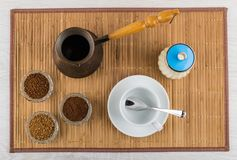 Bowls with instant and ground coffee, turka, sugar bowl, cup. Bowls with instant and ground coffee, turka, sugar bowl, empty cup, spoon on bamboo mat. Top view Royalty Free Stock Photos