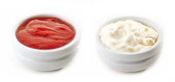 Bowls of ketchup and mayonnaise Stock Photos