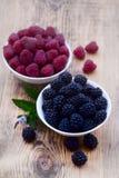 Bowls overflowing with summer berries like raspberries and blackberries. Stock Photo