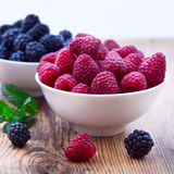 Bowls overflowing with summer berries like Stock Photography