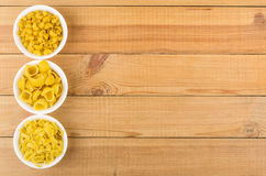 Bowls with pasta from left side wooden table Royalty Free Stock Images