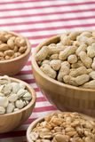 Bowls of peanuts, almonds, pistachios, cashews on red checkered Royalty Free Stock Images