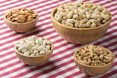 Bowls of peanuts, almonds, pistachios, cashews on red checkered Stock Photo