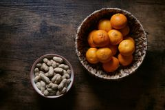 Bowls of peanuts and clementines on rustic table royalty free stock photo