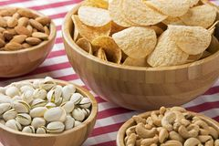 Bowls of potato chips, almonds, pistachios, cashews on red check Royalty Free Stock Photo