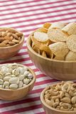 Bowls of potato chips, almonds, pistachios, cashews on red check Royalty Free Stock Photos