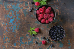 Bowls of raspberries and blueberries. Ceramic bowls of fresh raspberries and blueberries over old wooden textured background. Top view with copy space Stock Photography
